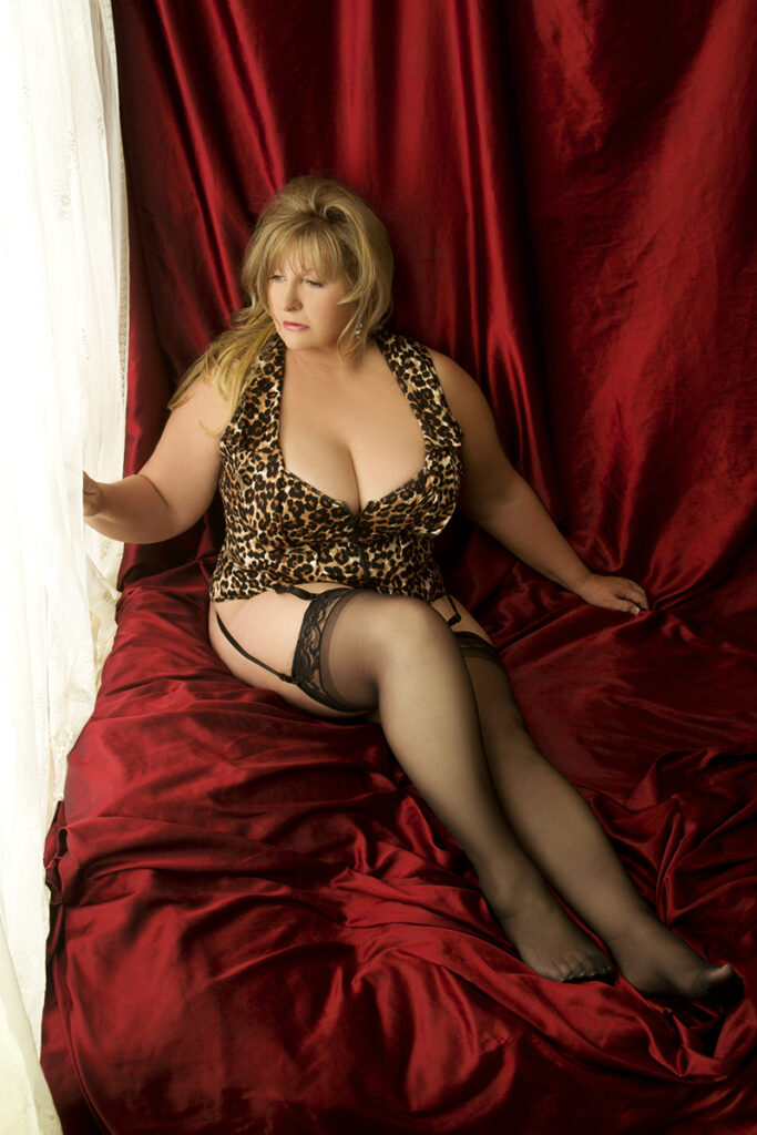 Inner Spirit Photo by Mark Laurie Boudoir plus size woman in leopard print lingerie by window in red bed set in Calgary studio.