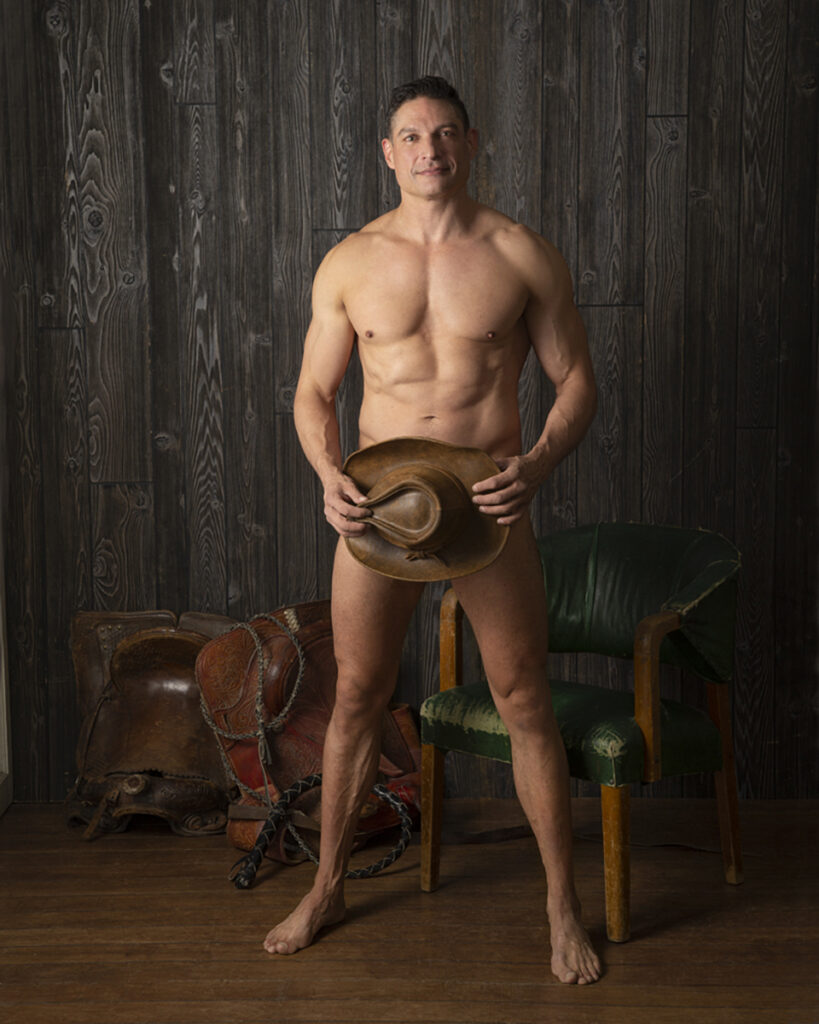 Inner Spirit Photo by Mark Laurie Boudoir of nude man with hat over his privates in western set in Calgary studio.