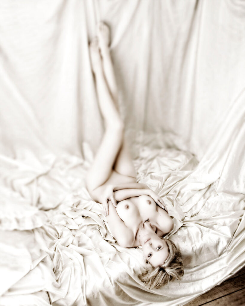 Inner Spirit Photo by Mark Laurie Boudoir nude woman lays in white bed on back, legs up, arms crossed looking at camera in Calgary studio.