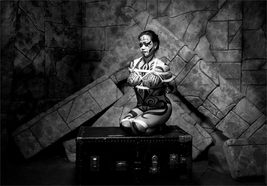 Inner Spirit Photo by Mark Laurie Boudoir nude body painted, tied with Shibari ropes kneels on a trunk in dramatic set in black and white in Calgary