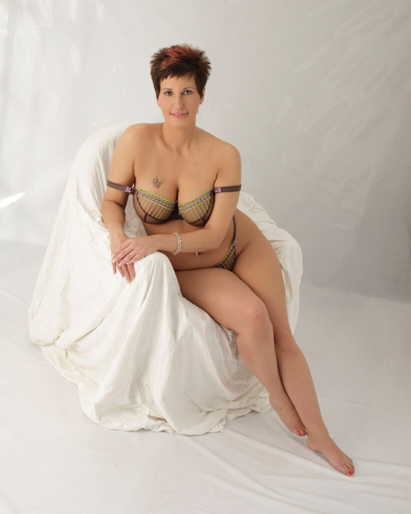 Inner Spirit Photo Boudoir by Mark Laurie plus sized woman in lingerie on white covered chair in hi-key set in Calgary, Canada.