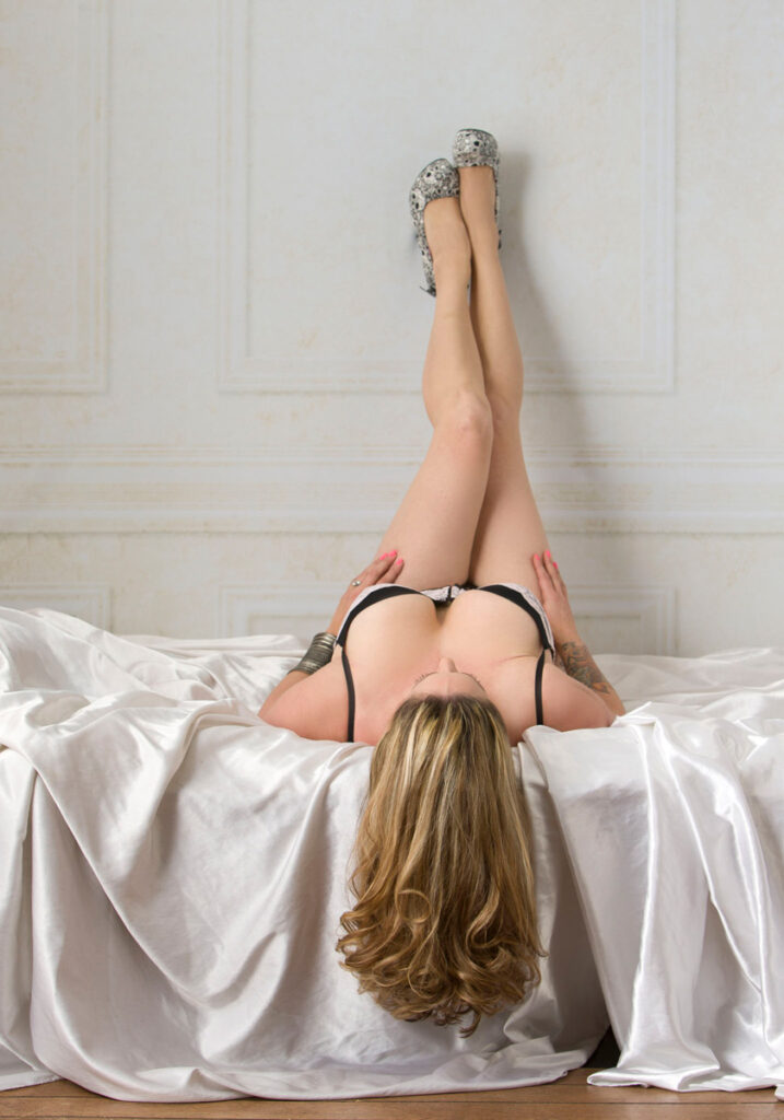 Inner Spirit Photo by Mark Laurie boudoir bed set with woman in lingerie with legs up on wall, hair hanging down in Calgary studio