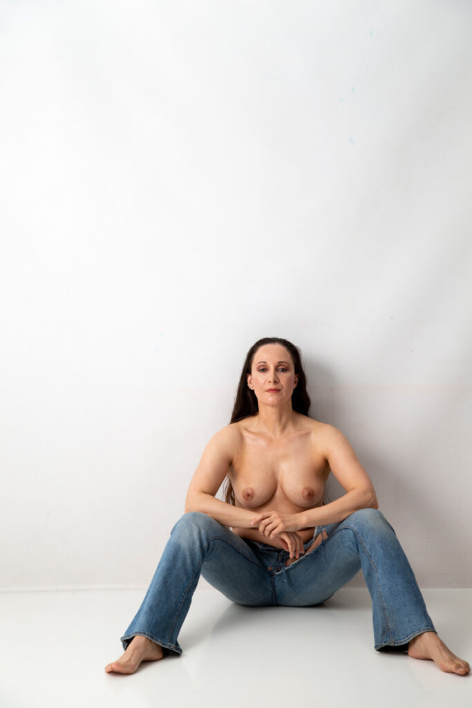 Inner Spirit Photo by Mark Laurie Boudoir of woman topless sitting in blue jeans in white set arms on knees in Calgary studio