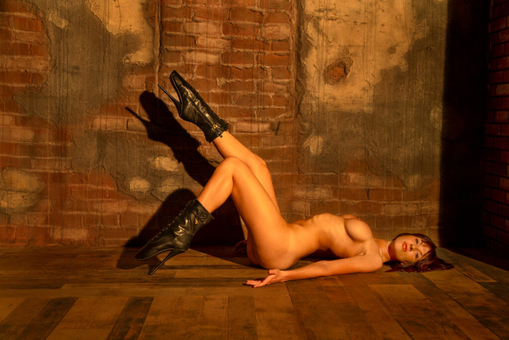 Inner Spirit Photo by Mark Laurie Boudoir nude women lays on wood floor with black boots kicking up in Calgary studio.