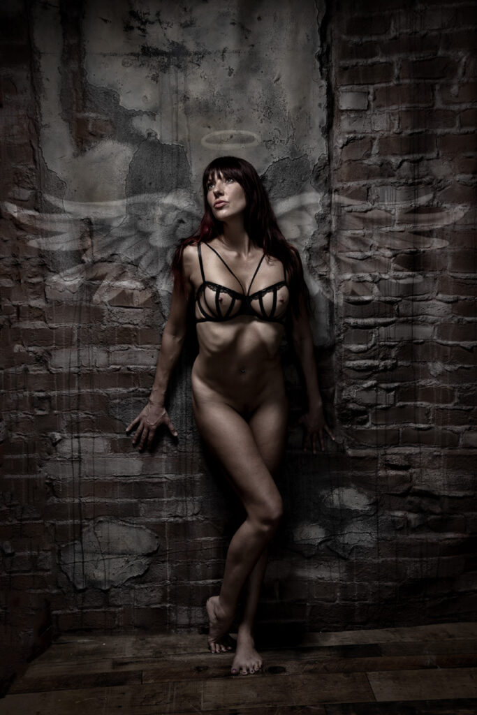 Inner Spirit Photo by Mark Laurie Boudoir shadowy nude leaning against brick wall with graffiti wings and halo painted behind her in Calgary studio