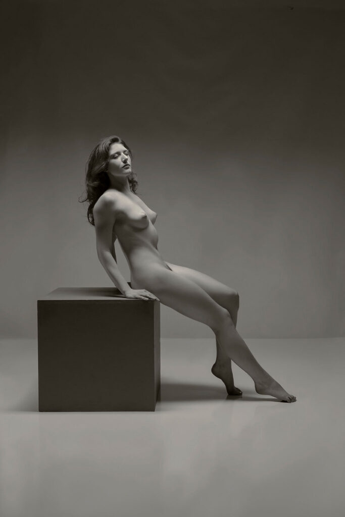 Inner Spirit Photo by Mark Laurie Boudoir artistic nude woman leaning back sitting on a gray cube in Calgary, Canada studio.