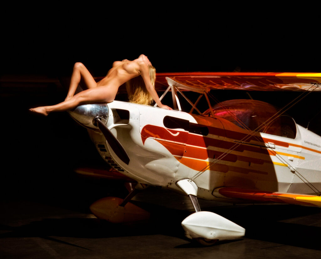Inner Spirit Photo by Mark Laurie Boudoir nude woman sitting on nose of small plane head back, arms braced, legs out in Calgary, Canada.