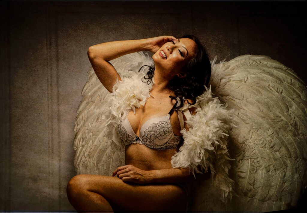 Inner Spirit Photo by Mark Laurie Boudoir of woman in lingerie with real feather wings looking up arm at forehead in Calgary, Canada studio.