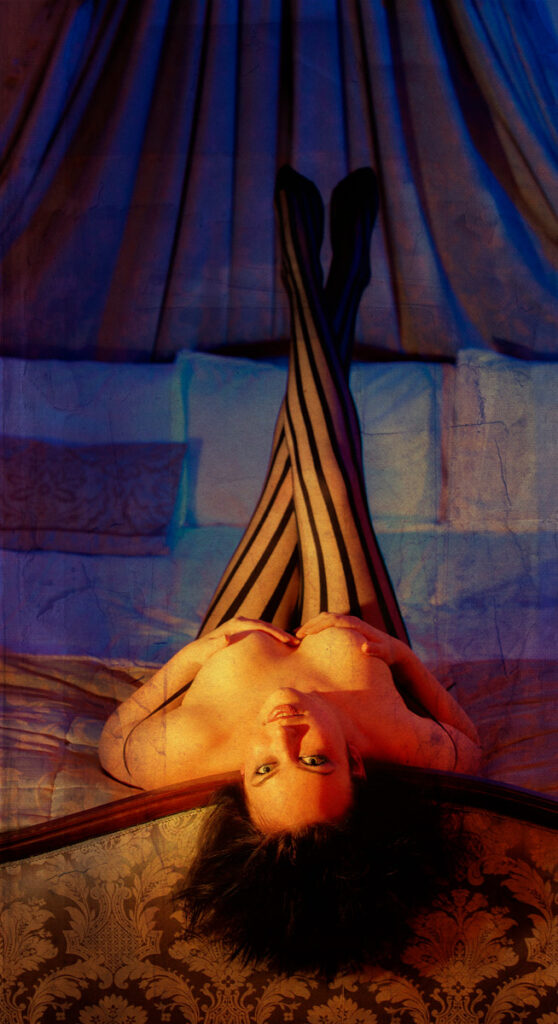 Inner Spirit Photo by Mark Laurie Boudoir partly nude woman in stripe stockings, legs up in bed looking back at camera in Canada.