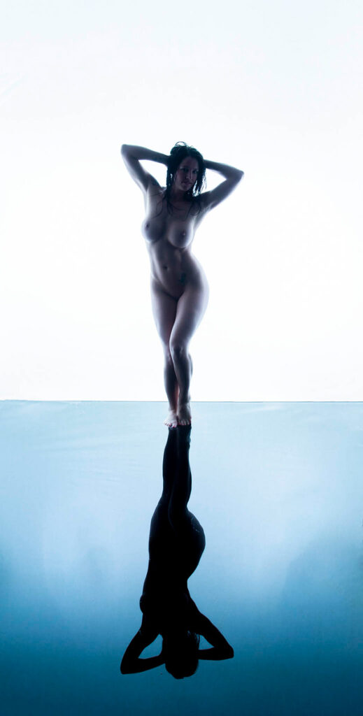 Inner Spirit Photo by Mark Laurie Boudoir nude stands in wet set with reflection at her feet in Calgary studio.