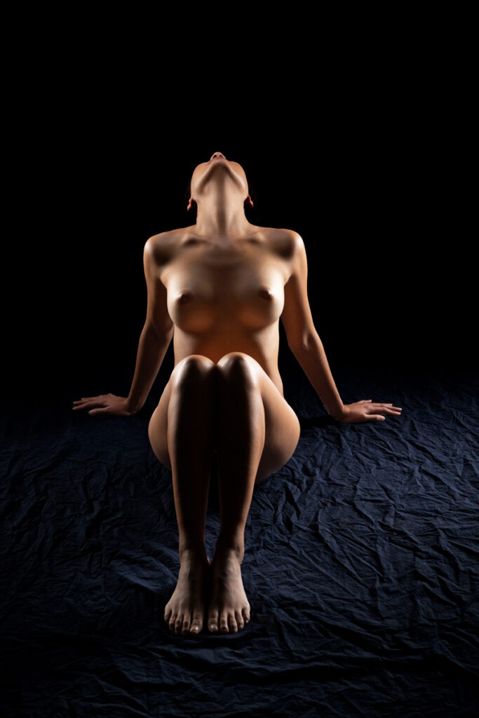 Inner Spirit Photo by Mark Laurie Boudoir shadowy nude woman sits on floor, head back out of sight, arms bracing, knees up in Calgary studio.