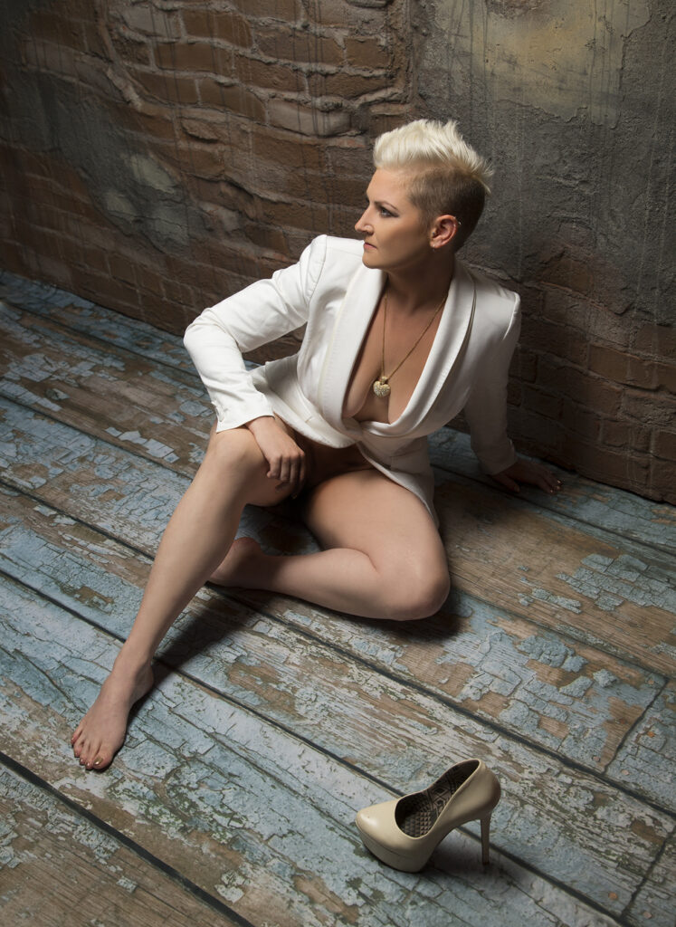 Inner Spirit Photo by Mark Laurie Boudoir nude woman in white coat sits on rough blue flooring with one shoe in Calgary studio.